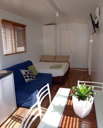 Modern style relocatable cabin for rent with furniture. Featuring a couch, double bed and kitchen table that sits four people. Suitable for a couple looking for cheap accommodation.